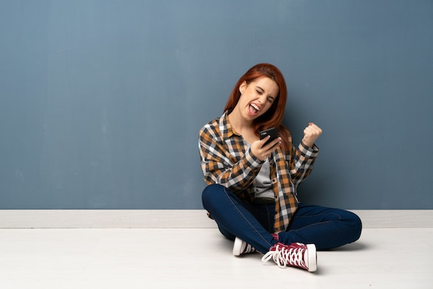 Рыжая молодая женщина сидит на полу с телефоном в победной позиции