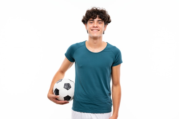 多くの笑みを浮かべて孤立した白い壁の上の若いフットボール選手男