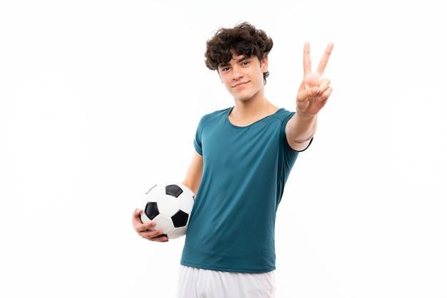 笑みを浮かべて、勝利のサインを示す分離の白い壁の上の若いフットボール選手男