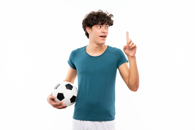 指を持ち上げながら解決策を実現しようとしている孤立した白い壁の上の若いフットボール選手男