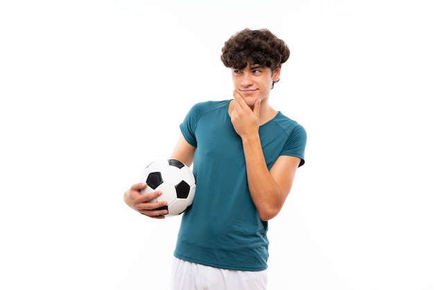 アイデアを考えて孤立した白い壁の上の若いフットボール選手男