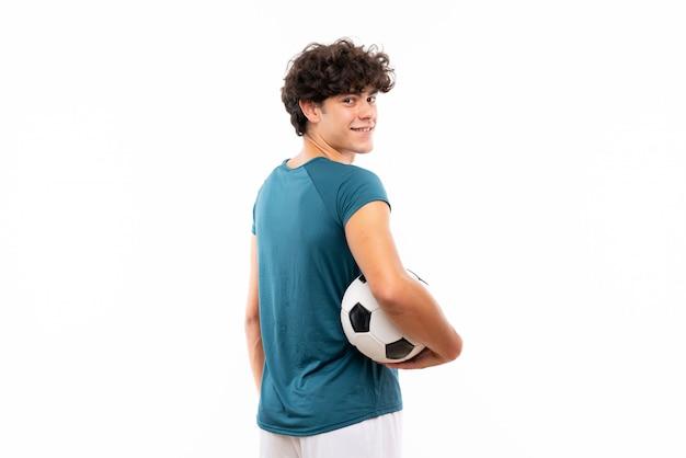 孤立した白い壁の上の若いフットボール選手男