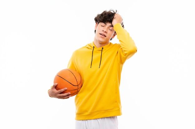 孤立した白い壁の上の若いバスケットボールプレーヤーの男は何かを実現し、解決策を意図