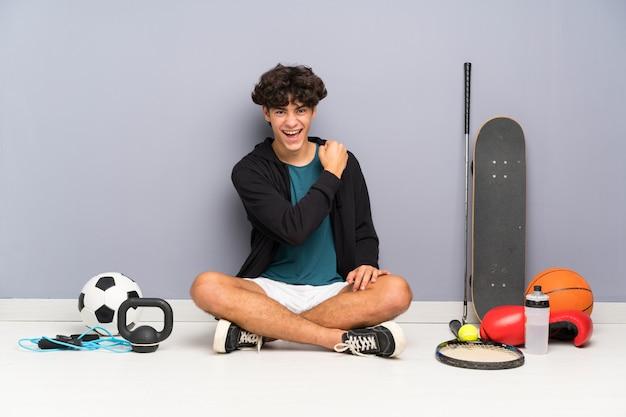 勝利を祝う多くのスポーツ要素の周りの床に座っている若いスポーツ男