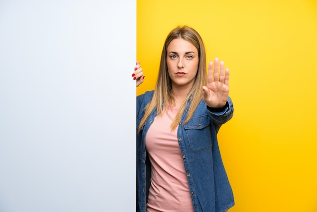 彼女の手で停止ジェスチャーを作る空のプラカードを保持している若い女性