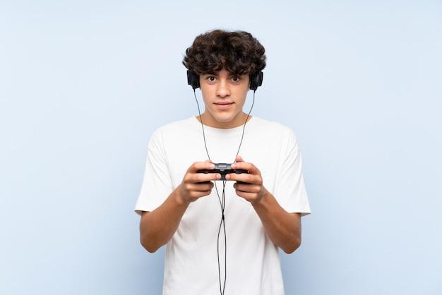 孤立した青い壁を越えてビデオゲームコントローラーで遊ぶ若い男