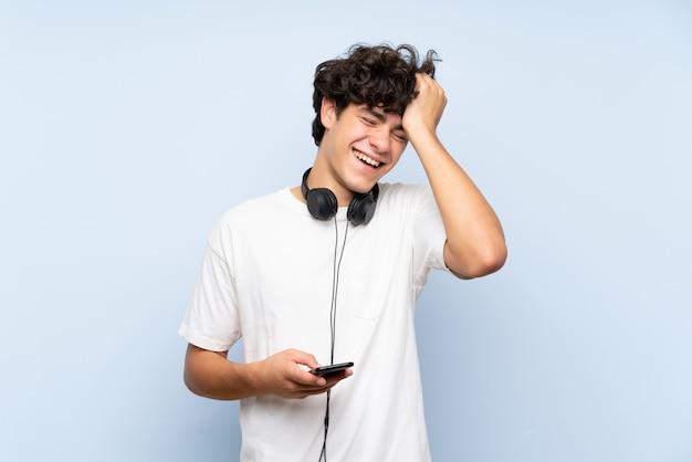 孤立した青い壁の上の携帯電話で音楽を聴く若い男が何かを実現し、解決策を意図しています