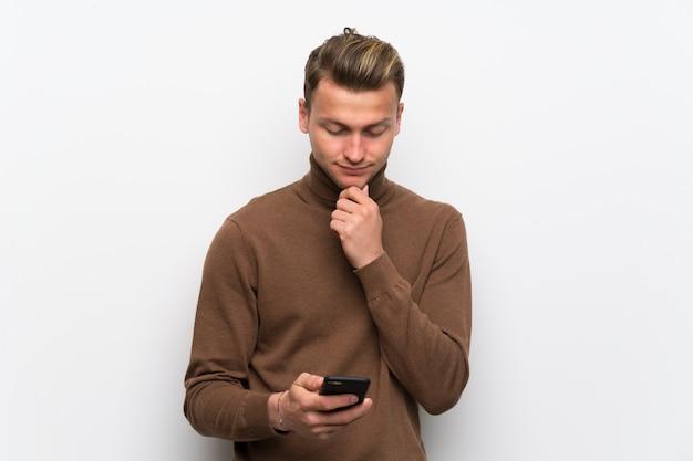 携帯電話と思考で孤立した白い壁に金髪の男