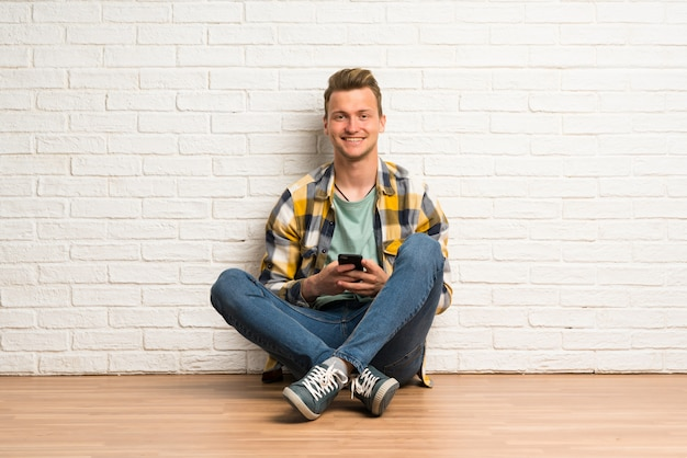 携帯電話でメッセージを送信する床に座っている金髪の男