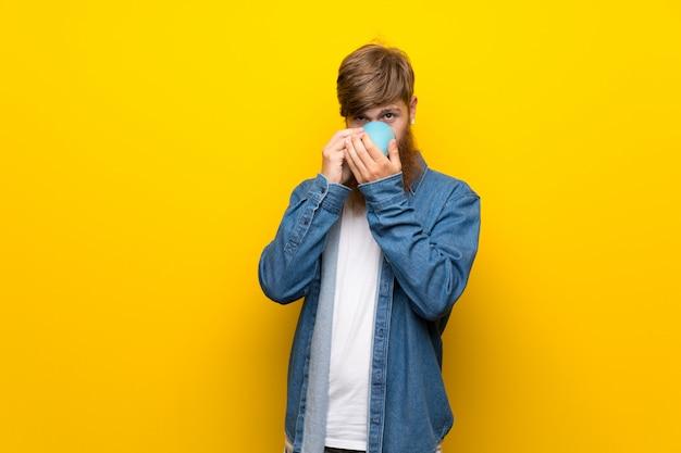 コーヒーの熱いカップを保持している孤立した黄色の壁の上の長いひげを持つ赤毛の男