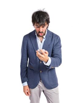 白い背景の上で携帯電話に話す怒っている男