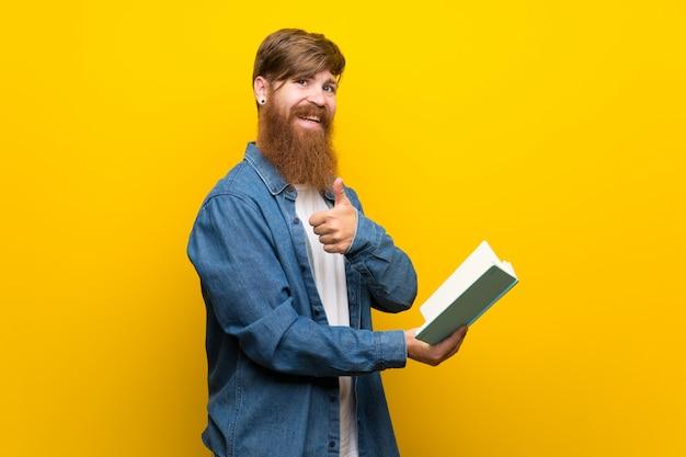 孤立した黄色の壁を押しながら本を読んで長いひげを持つ赤毛の男