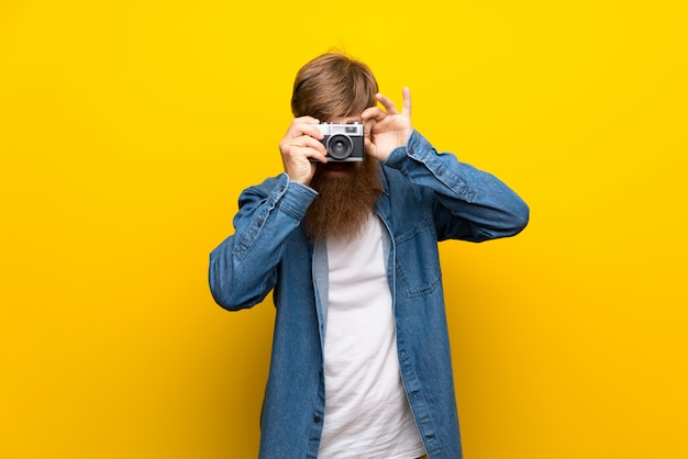 カメラを保持している孤立した黄色の壁の上の長いひげを持つ赤毛の男