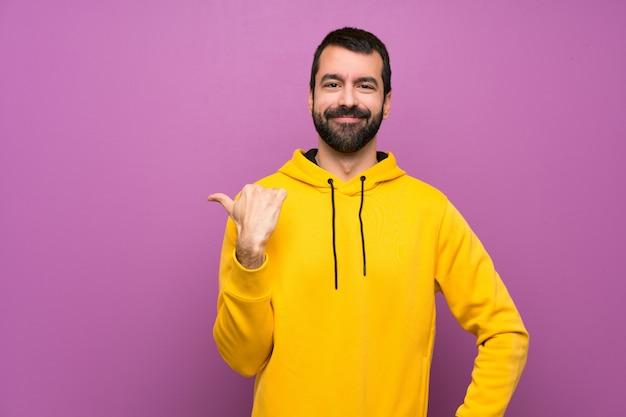 製品を提示する側を指している黄色のスウェットシャツを持つハンサムな男