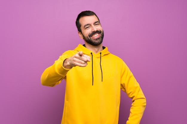 黄色のスウェットシャツを持つハンサムな男は自信を持って表現であなたに指を指す