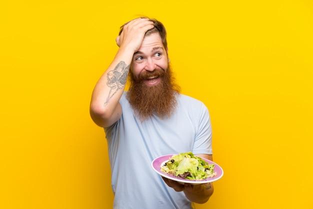 長いひげと孤立した黄色の壁にサラダと赤毛の男が何かを実現し、解決策を意図している