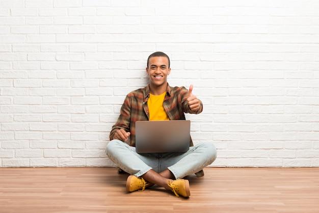 Афро-американский мужчина сидит на полу со своим ноутбуком, давая пальцы вверх жест, потому что случилось что-то хорошее