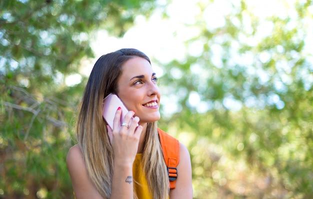 携帯電話に話している屋外でバックパックを持つ学生少女