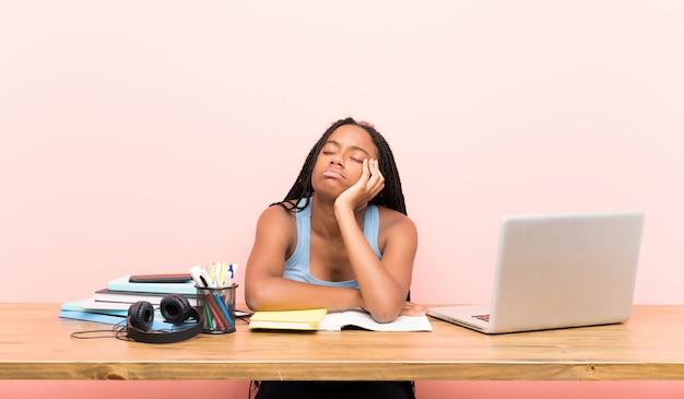 Афро-американский подросток студент девушка с длинными заплетенными волосами на своем рабочем месте