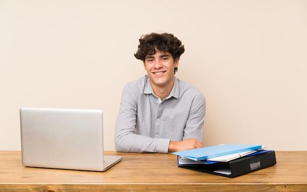 多くの笑みを浮かべてラップトップを持つ若い学生男