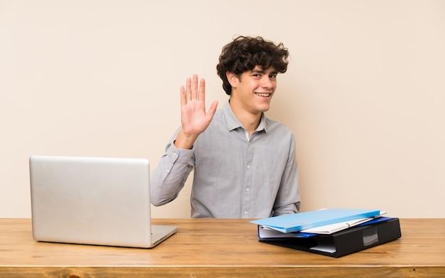 幸せな表情で手で敬礼のラップトップを持つ若い学生男