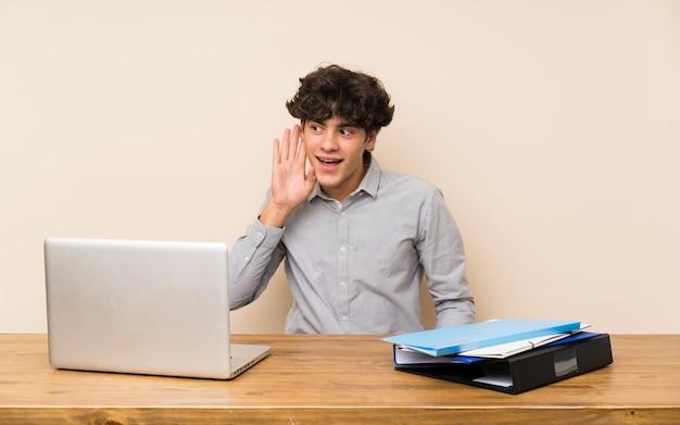 耳に手を置くことによって何かを聞いてラップトップを持つ若い学生男