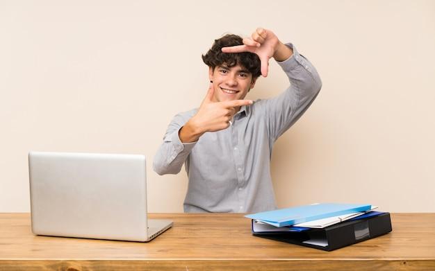 顔の焦点を合わせてラップトップを持つ若い学生男。フレーミングシンボル