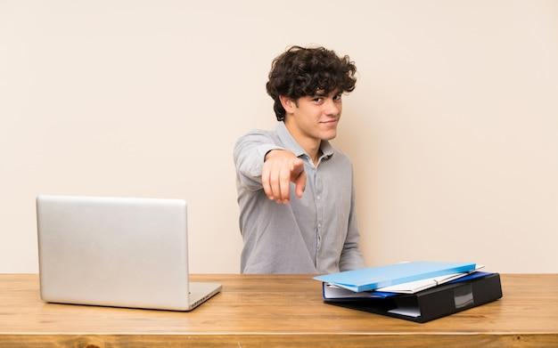 ラップトップを持つ若い学生男が自信を持って表現であなたに指を指す