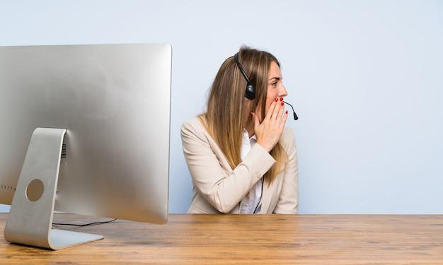 Молодая телемаркетер женщина кричит с широко открытым ртом