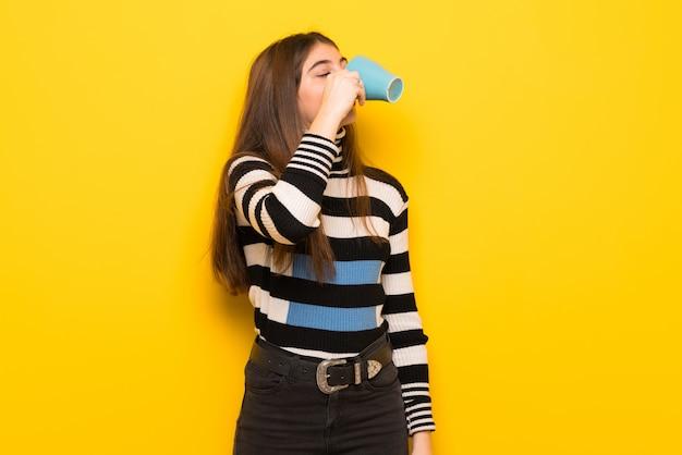 熱い一杯のコーヒーを保持している黄色の壁の上の若い女性