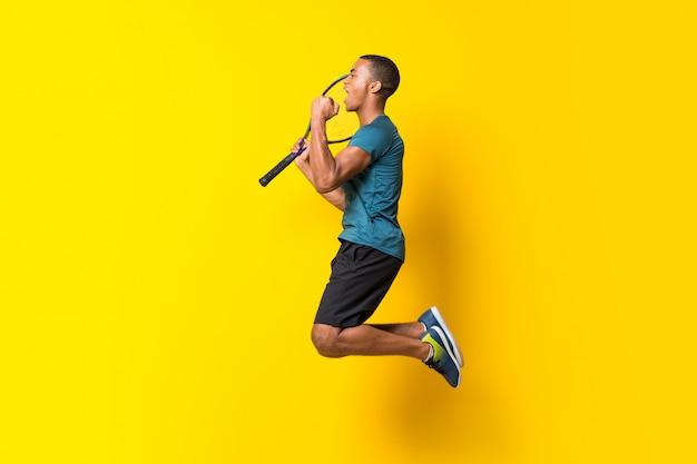 分離された黄色の上のアフロアメリカンテニスプレーヤー男