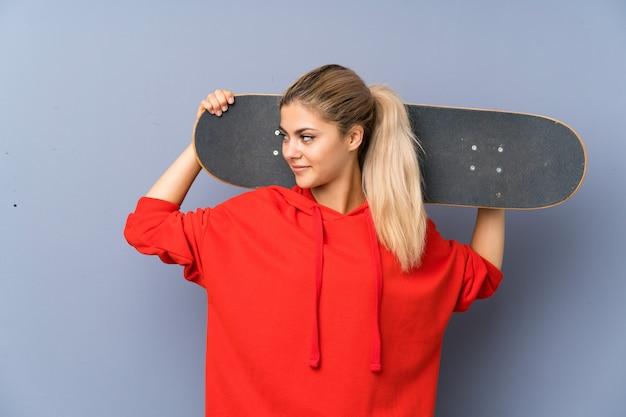 灰色の壁の上の金髪のティーンエイジャースケーターの女の子