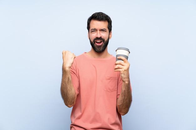勝者の位置で勝利を祝う分離された青の上のテイクアウェイコーヒーを保持しているひげを持つ若者