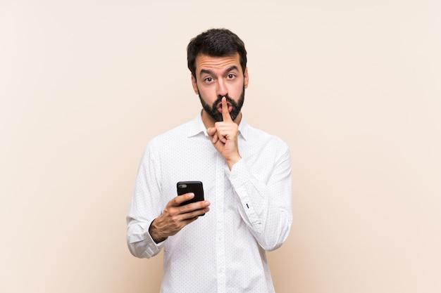 Молодой человек с бородой держит мобильный телефон, показывая знак жеста молчания, положив палец в рот