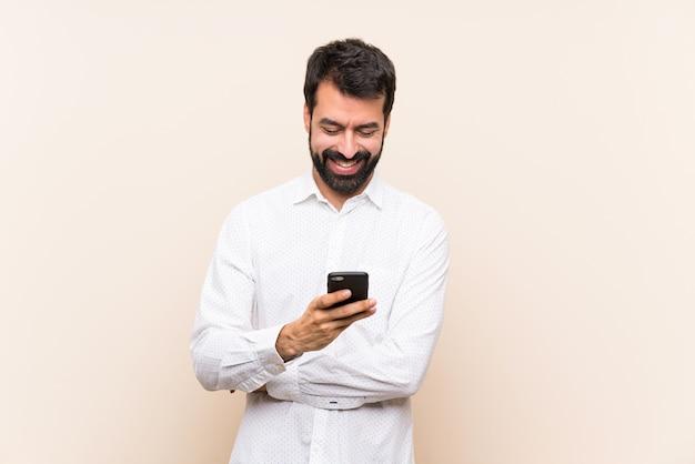 Молодой человек с бородой держит мобильный телефон, отправив сообщение с мобильного телефона