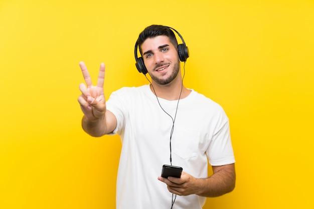 笑顔と勝利のサインを示す分離の黄色の壁を越えて携帯電話で音楽を聴く若いハンサムな男