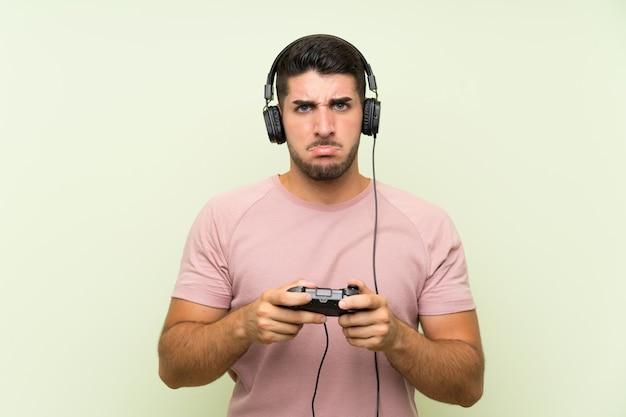孤立した緑の壁の上のビデオゲームコントローラーで遊ぶ若いハンサムな男