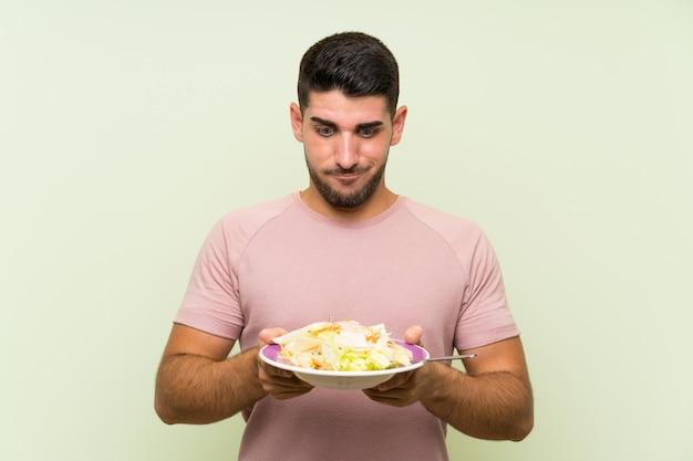 孤立した緑の壁の上のサラダと若いハンサムな男