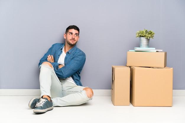 笑っているボックスの間で新しい家に移動するハンサムな若い男