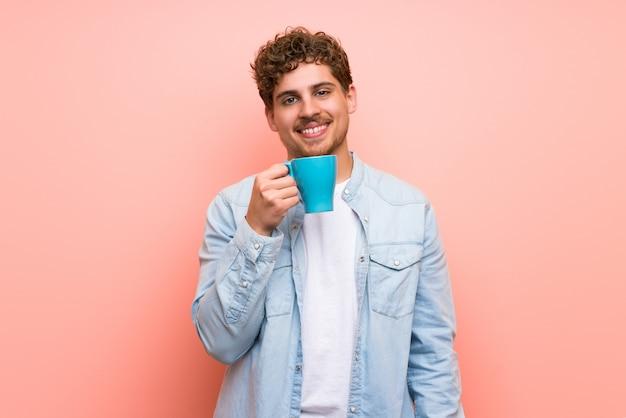 熱い一杯のコーヒーを保持しているピンクの壁の上の金髪の男