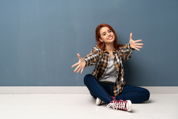 若い赤毛の女性が床に座って提示し、手に来るように招待