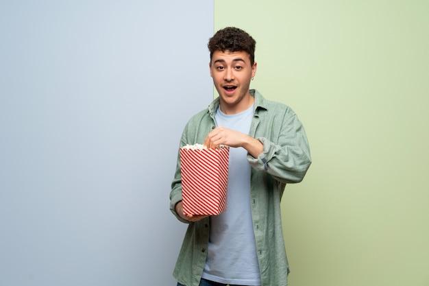 Молодой человек над синим и зеленым удивлен и ест попкорн