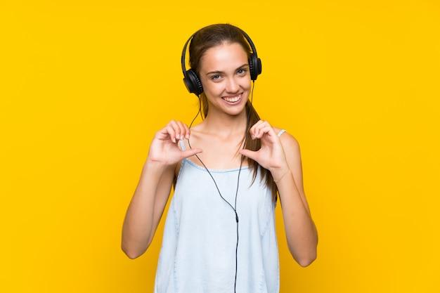 孤立した黄色の壁の誇りと自己満足で音楽を聴く若い女性