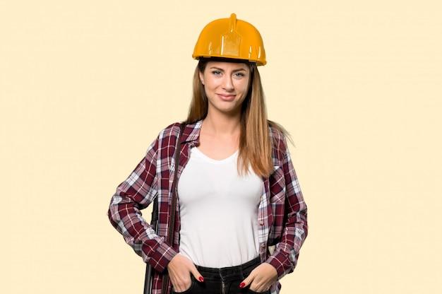 孤立した黄色の前を見て笑っている建築家の女性