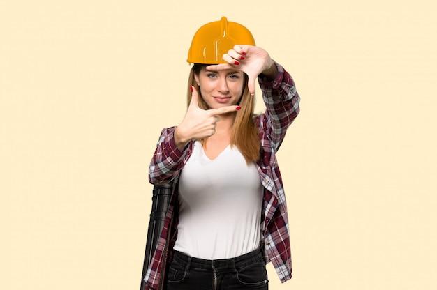 建築家の女性の顔に焦点を当てます。孤立した黄色の上のフレーミングシンボル