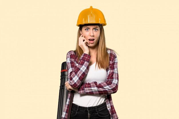 Архитектор женщина удивлен и шокирован, глядя прямо над желтым