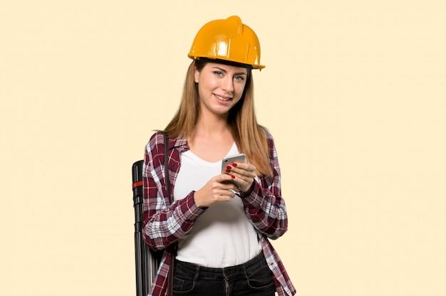 孤立した黄色の上の携帯電話でメッセージを送信する建築家女性