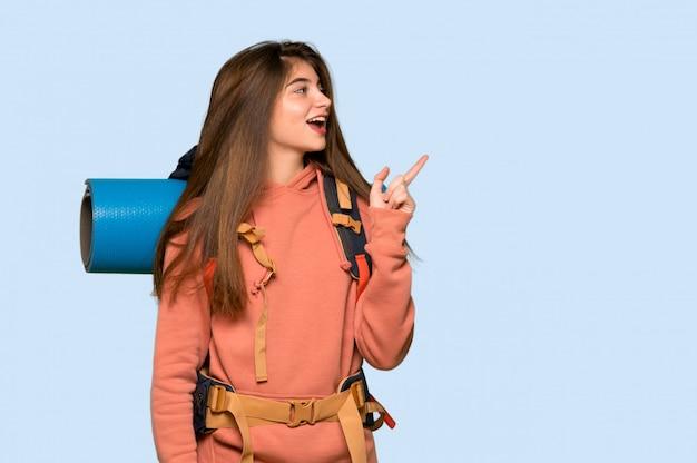 ハイカーの女の子が青の横位置で側に指を指す