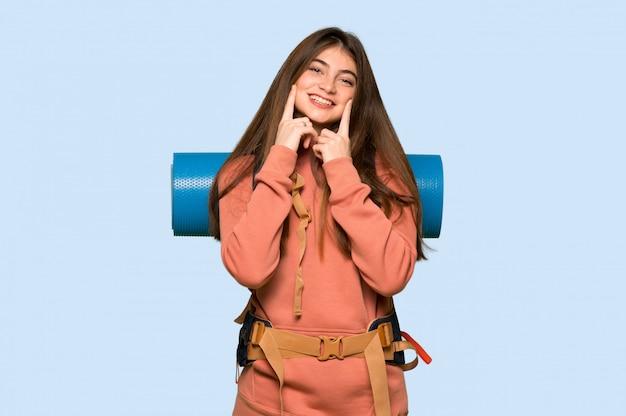 青の幸せで楽しい表情で笑っているハイカーの女の子