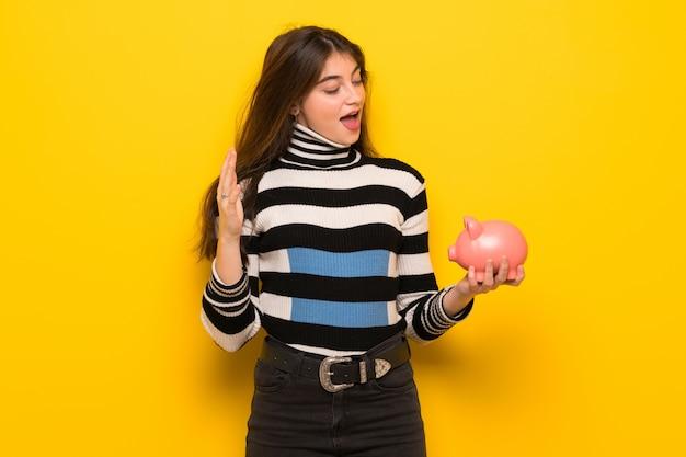 Молодая женщина за желтой стеной удивлен, держа копилку